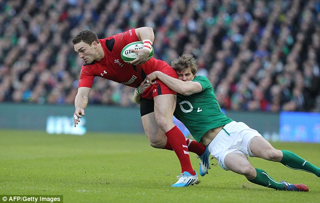 Going nowhere: Wales wing George North (left) is tackled his Irish reflection Andrew Trimble