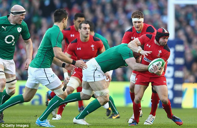 Under pressure: Wales star Leigh Halfpenny (right) tries to pass a round out of a tackle