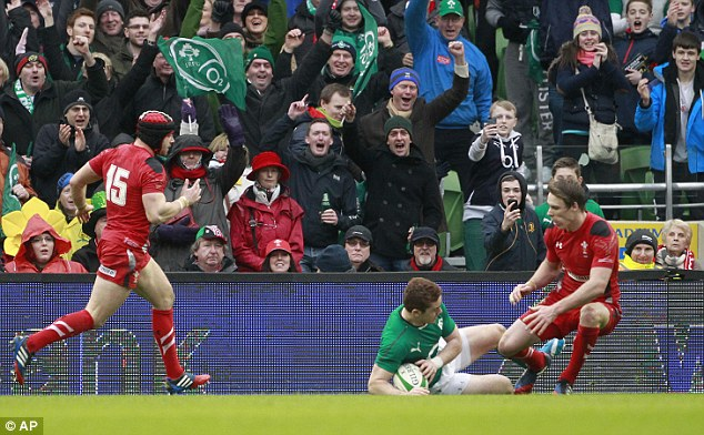 All over: Ireland fans applaud as Paddy Jackson (centre) scores a game's second try